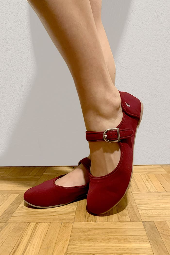 Feet wearing burgundy shoes in white background