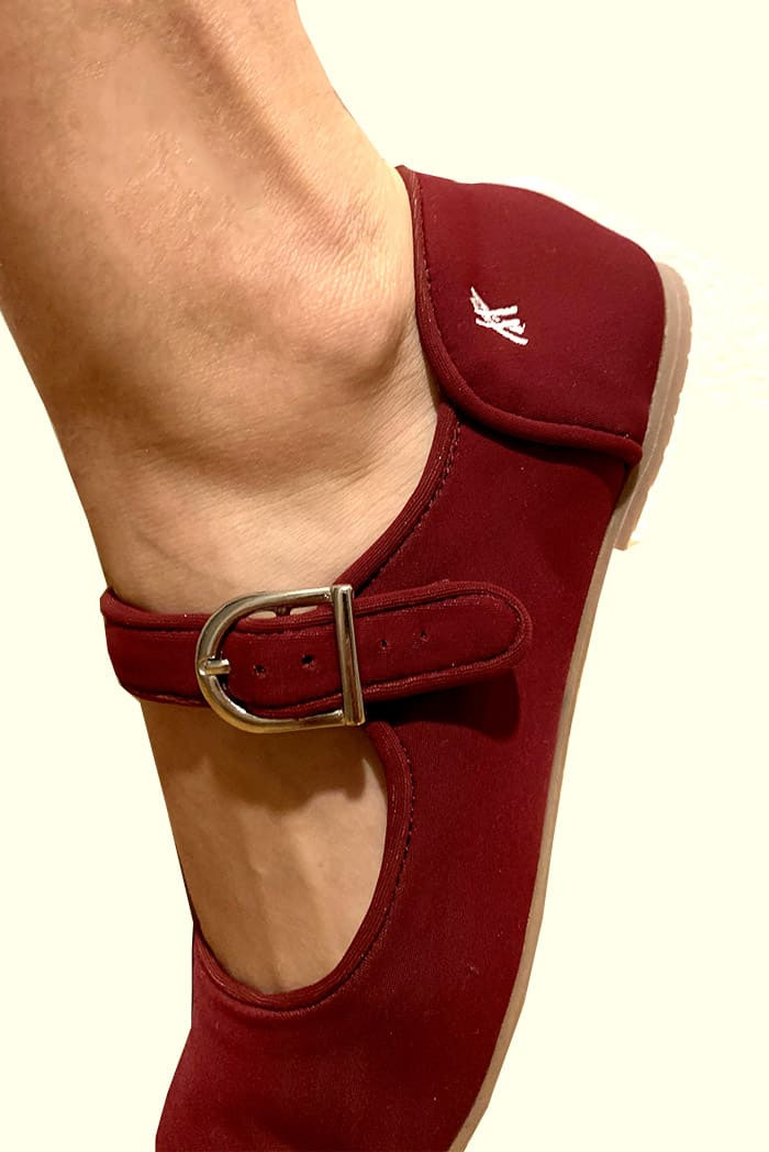 Foot wearing burgundy shoe in white background