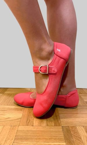 feet wearing bright pink shoes in white background