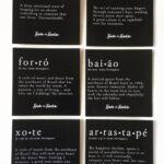 black paper stickers with definition of sentences: baião, forró, xote, cafuné, saudade, arrastapé