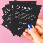 Hand holding black stickers with the definitions of Cafuné, Saudade, Forró, Baião, Xote and Arrastapé