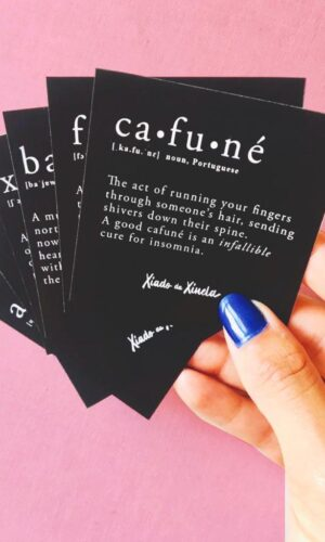 Hand holding black stickers with the definitions of Cafuné, Saudade, Forró, Baião, Xote and Arrastapé
